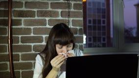 Jonge bedrijfsvrouw die op kantoor met laptop niezen stock videobeelden