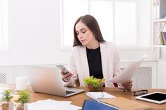 Jonge bedrijfsvrouw die salade eten op kantoor royalty-vrije stock afbeeldingen