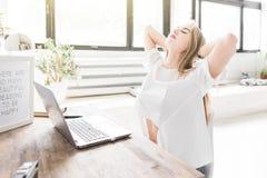 Jonge bedrijfsvrouw die thuis achter laptop werken en haar handen uitrekken Creatieve Skandinavische stijlwerkruimte royalty-vrije stock afbeeldingen