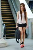 Jonge bedrijfsvrouw die voor roltrap lopen stock foto's