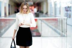 Jonge bedrijfsvrouw in een stormloop, die in tijd op polshorloge kijken Stock Fotografie