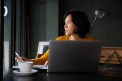 Jonge bedrijfsvrouw in gele kledingszitting bij lijst in koffie stock foto