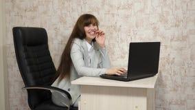 jonge bedrijfsvrouw in haar werkplaats Mooie onderneemstervrouw in bedrijfscorrespondentie op laptop Jong meisje stock videobeelden