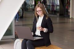 Jonge bedrijfsvrouw met een laptop het drinken koffie stock afbeelding