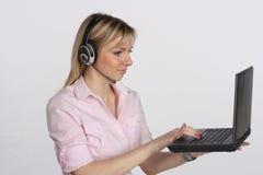 Jonge bedrijfsvrouw met hoofdtelefoon en laptop Royalty-vrije Stock Afbeeldingen