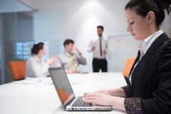 Jonge bedrijfsvrouw op vergadering die laptop computer met behulp van Stock Foto