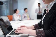Jonge bedrijfsvrouw op vergadering die laptop computer met behulp van Stock Afbeelding