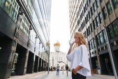 Jonge bedrijfsvrouw tijdens een onderbreking het drinken koffie in openlucht Royalty-vrije Stock Foto's