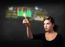 Jonge bedrijfsvrouw wat betreft kleurrijke grafieken en diagrammen Stock Foto