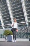 Jonge bedrijfsvrouw in zonnebril met zak in de stad die zich met notitieboekje bevindt royalty-vrije stock afbeeldingen
