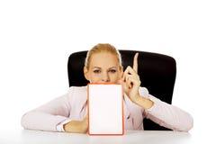 Jonge bedrijfsvrouwenzitting achter het bureau en holding een raad met verbod stock afbeeldingen
