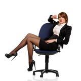 Jonge bedrijfsvrouwenzitting als bureauvoorzitter Royalty-vrije Stock Afbeeldingen