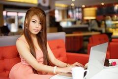 Jonge bedrijfsvrouwenzitting i koffie met haar laptop royalty-vrije stock foto
