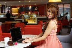 Jonge bedrijfsvrouwenzitting in koffie met haar laptop stock foto's