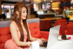 Jonge bedrijfsvrouwenzitting in koffie met haar laptop royalty-vrije stock afbeelding