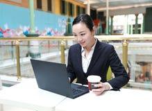 Jonge bedrijfsvrouwenzitting in koffiewinkel bij houten lijst, het drinken koffie Op lijst is laptop stock afbeeldingen