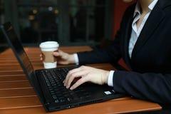 Jonge bedrijfsvrouwenzitting in koffiewinkel bij houten lijst, het drinken koffie Op lijst is laptop royalty-vrije stock fotografie