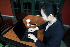 Jonge bedrijfsvrouwenzitting in koffiewinkel bij houten lijst, het drinken koffie Op lijst is laptop stock afbeelding
