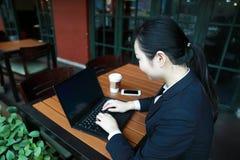 Jonge bedrijfsvrouwenzitting in koffiewinkel bij houten lijst, het drinken koffie Op lijst is laptop royalty-vrije stock afbeelding