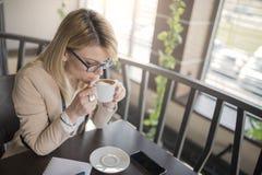 Jonge bedrijfsvrouwenzitting in koffiewinkel en het drinken van een kop van koffie stock foto's