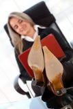 Jonge bedrijfsvrouwenzitting op bureau Stock Foto