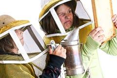 Jonge beekeepers die een bijenbijenkorf kalmeren Stock Afbeelding