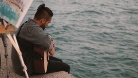 Jonge begaafde paarzitting op de kust van het overzees en het doen van hobby Vrouwentekening, man het spelen gitaar stock footage