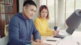 Jonge beklemtoonde Aziatische paar het leiden financiën, die hun bankrekeningen herzien die laptop computer en calculator gebruik stock videobeelden