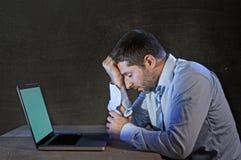 Jonge beklemtoonde zakenman die aan bureau met computerlaptop werken in frustratie en depressie Royalty-vrije Stock Foto