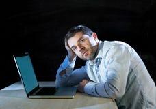 Jonge beklemtoonde zakenman die aan bureau met computerlaptop werken in frustratie en depressie Royalty-vrije Stock Afbeeldingen