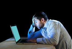 Jonge beklemtoonde zakenman die aan bureau met computerlaptop werken in frustratie en depressie Stock Foto