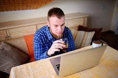 Jonge beroeps die Internet op zijn laptop surfen en whisky van een glas drinken royalty-vrije stock afbeelding