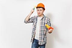 Jonge betrokken mens in beschermende oranje het stuk speelgoed van de bouwvakkerholding zaag en afstraffing zelf op hoofd met stu royalty-vrije stock fotografie