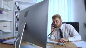 Jonge bezige bedrijfsmens die op mobiele telefoon en bureautelefoon spreken en nota's in notitieboekje maken terwijl het zitten b Royalty-vrije Stock Fotografie