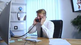 Jonge bezige bedrijfsmens die op mobiele telefoon en bureautelefoon spreken en nota's in notitieboekje maken terwijl het zitten b Stock Afbeelding