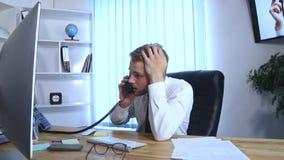 Jonge bezige bedrijfsmens die op mobiele telefoon en bureautelefoon spreken en nota's in notitieboekje maken terwijl het zitten b Royalty-vrije Stock Foto