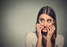 Jonge bezorgde onzekere aarzelende zenuwachtige vrouw die haar vingernagels bijten Stock Foto