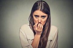 Jonge bezorgde onzekere aarzelende zenuwachtige vrouw die haar vingernagels bijten Royalty-vrije Stock Fotografie