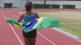 Jonge biracial winnaar die van de sportenconcurrentie op arena met vlag van Brazilië lopen stock videobeelden