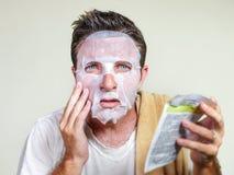 Jonge bizarre en grappige mens thuis proberend gebruikend schoonheidsdocument het gezichtsmasker het reinigen het leren het anti  stock foto's