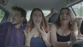 Jonge blije vrienden die en pret samen binnen een reizende auto hebben die van de reis van de de zomervakantie genieten dansen - stock footage