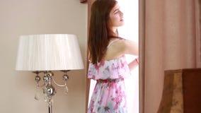 Jonge blije vrouw die de gordijnen open houden om uit groot licht venster thuis te kijken, draaiend om te bekijken en te glimlach stock footage