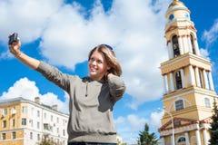 Jonge blije vrouw die zelf-portretfoto met gemakkelijk behandelde camera nemen tegen klokketoren van kerk in Rusland royalty-vrije stock afbeelding
