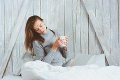 Jonge blogger of bedrijfsvrouw die thuis met sociale media, het drinken koffie in vroege ochtend in bed werken Royalty-vrije Stock Fotografie