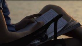 Jonge Blogger schrijft en zit op een Vouwende Stoel bij Zonsondergang stock footage