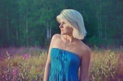 Jonge blond op een gebied van bloemen Stock Foto's