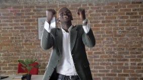 Jonge blonde Afrikaanse Amerikaanse modieuze zakenman die en in modern bureau, zekere en succesvolle arbeider dansen toejuichen stock footage