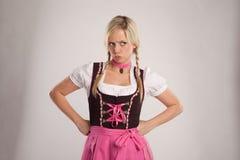 Jonge blonde boze vrouw met dirndlkostuum Royalty-vrije Stock Foto's