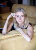Jonge blonde dameplaatsing op de leerbank Stock Afbeeldingen