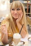 Jonge blonde in een koffie met lattemacchiato Royalty-vrije Stock Afbeelding
